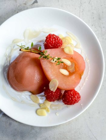 poached pears on a plate with raspberries