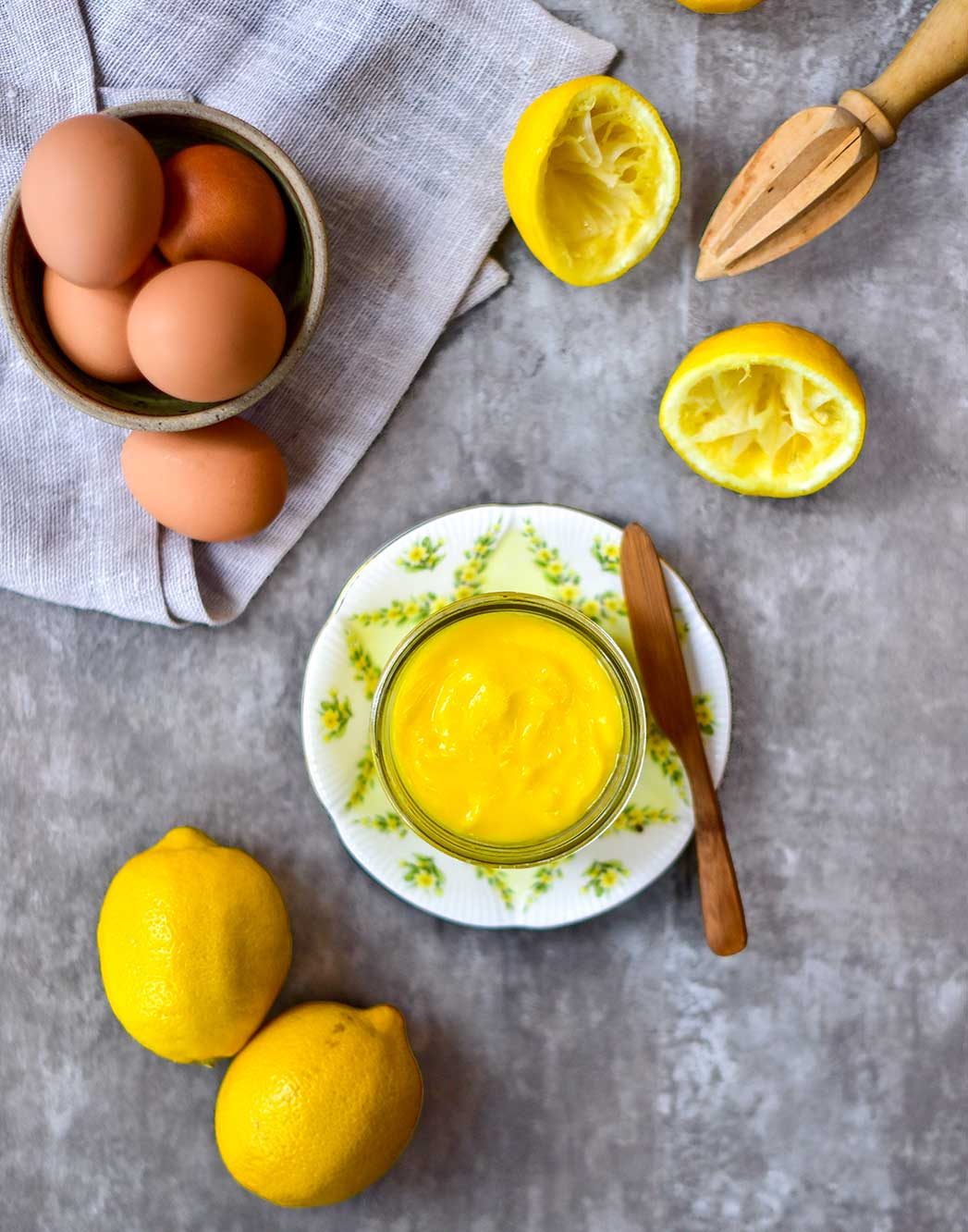 lemon curd with lemons and eggs on table