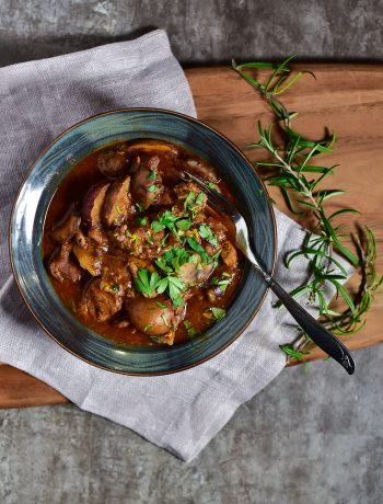 top view of a bowl of beef stew on a wooden cutting board with rosemary and a fork