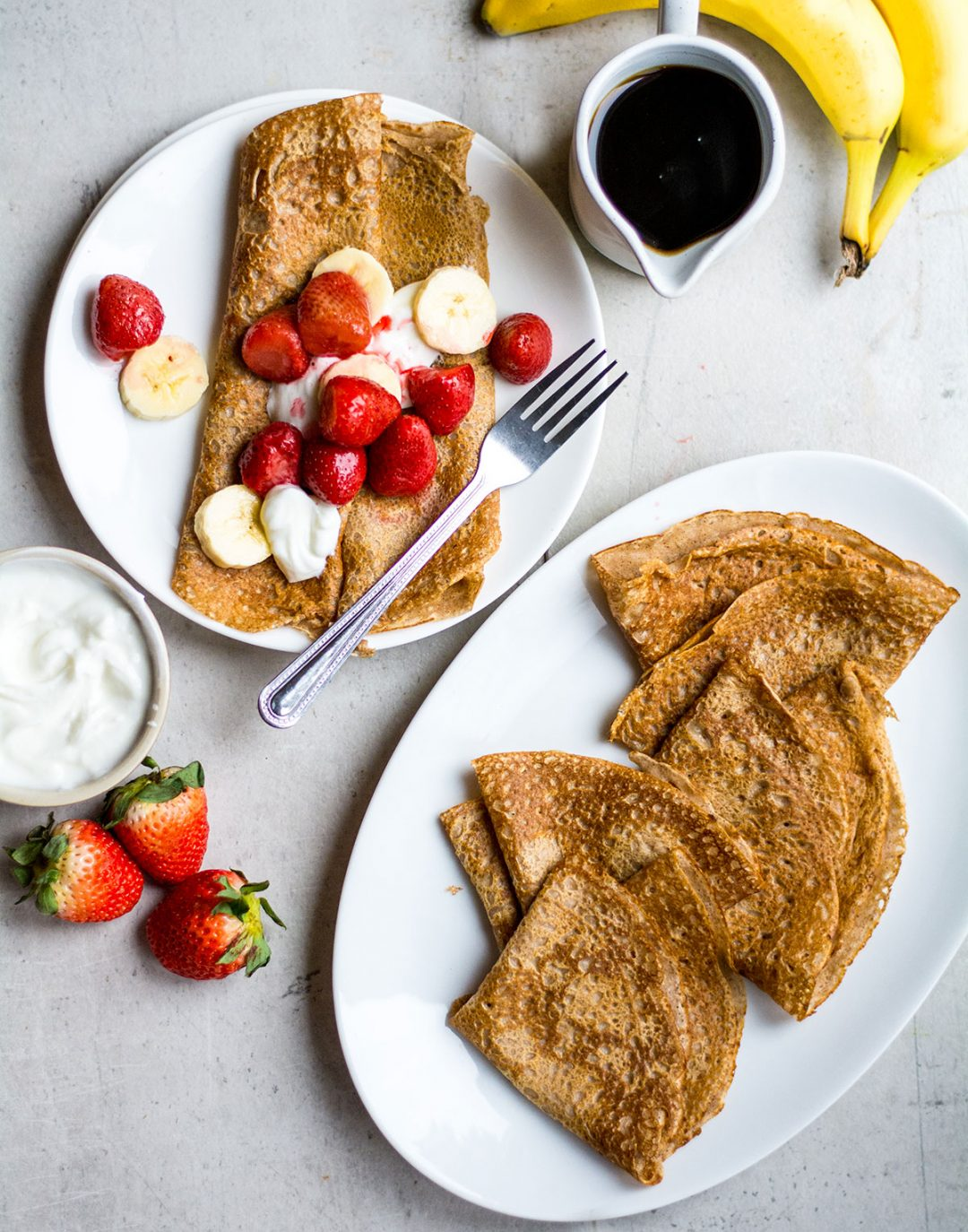 crepes on white background with strawberries and bananas