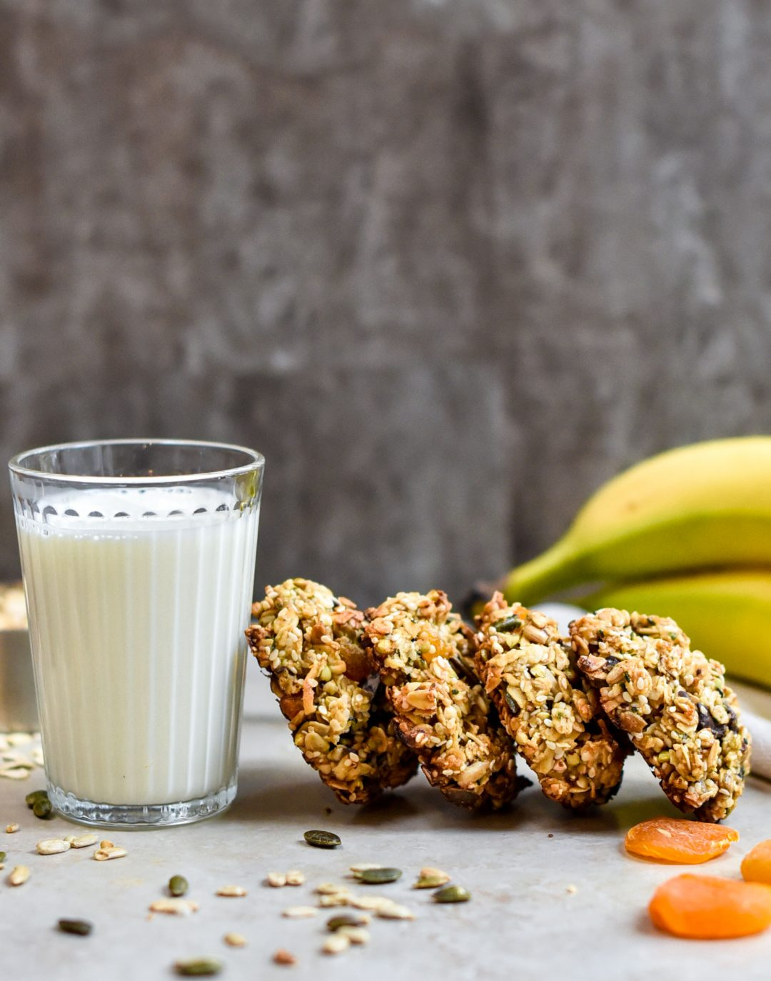 granola cookies leaning against glass of milk with bananas and seeds