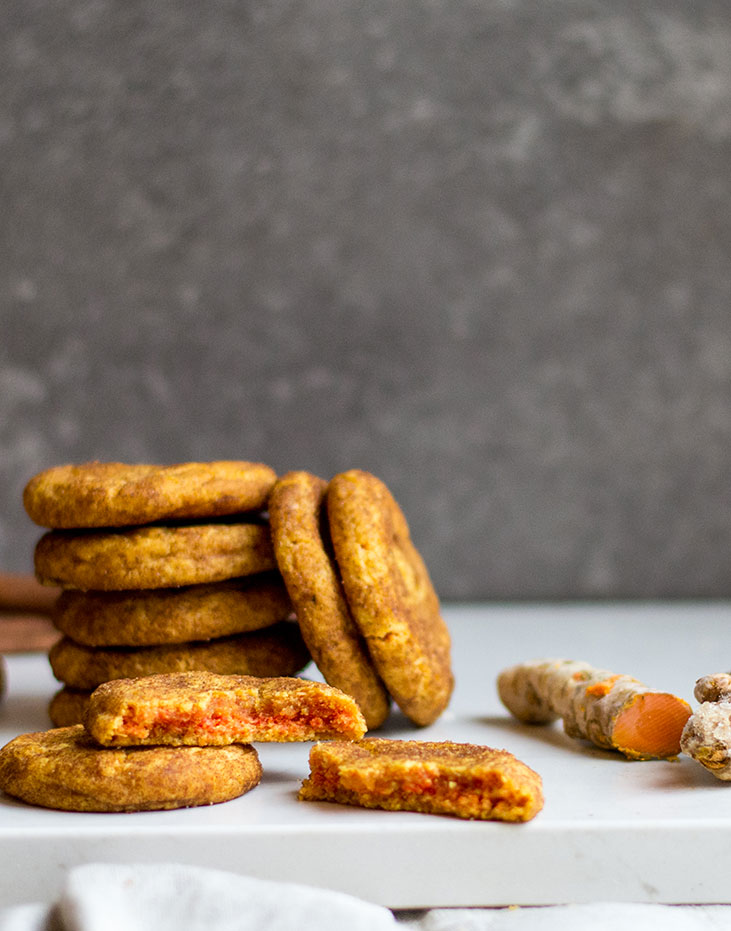 Close up of stack of cookies with turmeric beside it