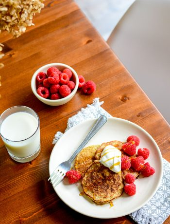 pancakes on wooden table with raspberries