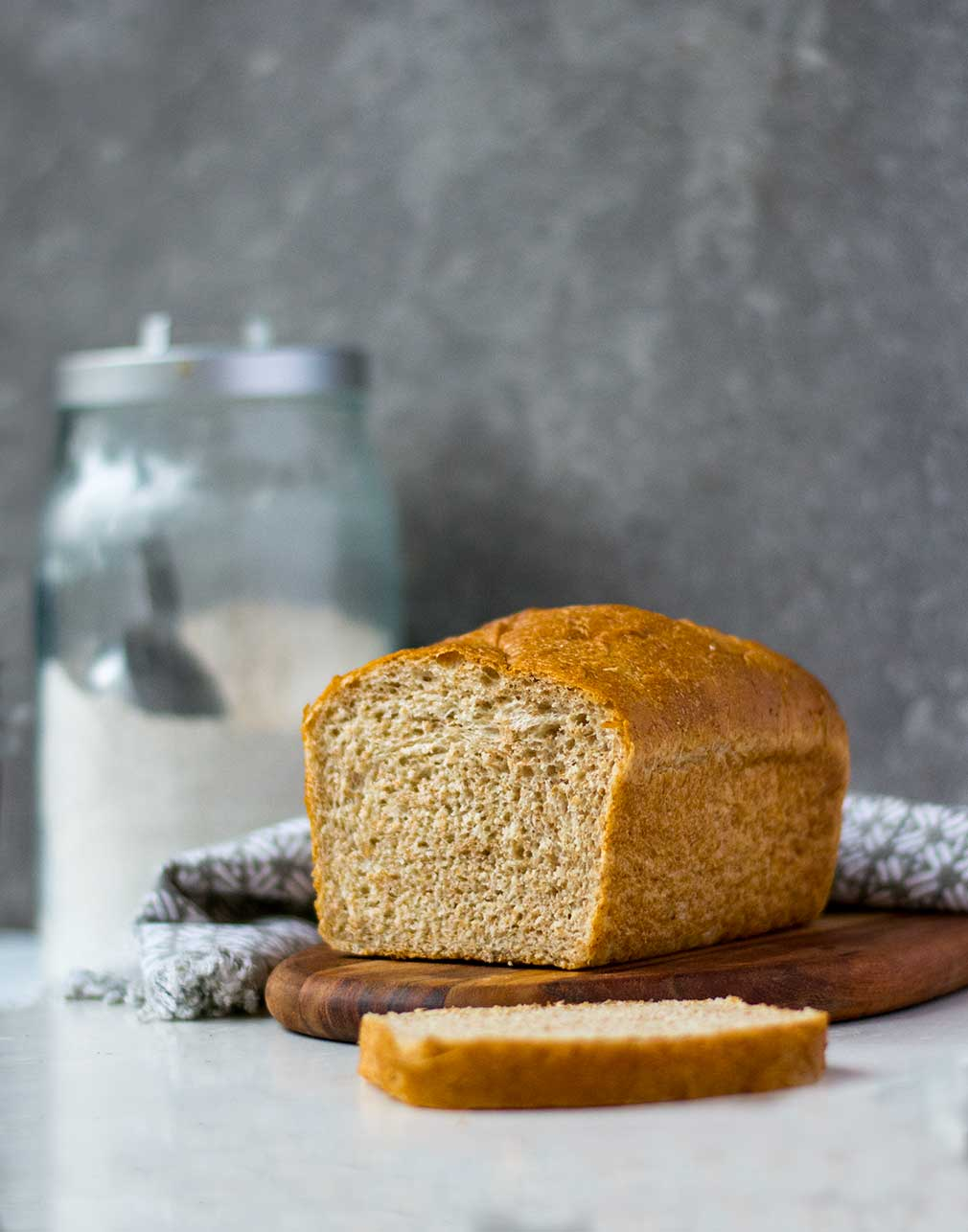 side view of whole wheat bread with flour in background