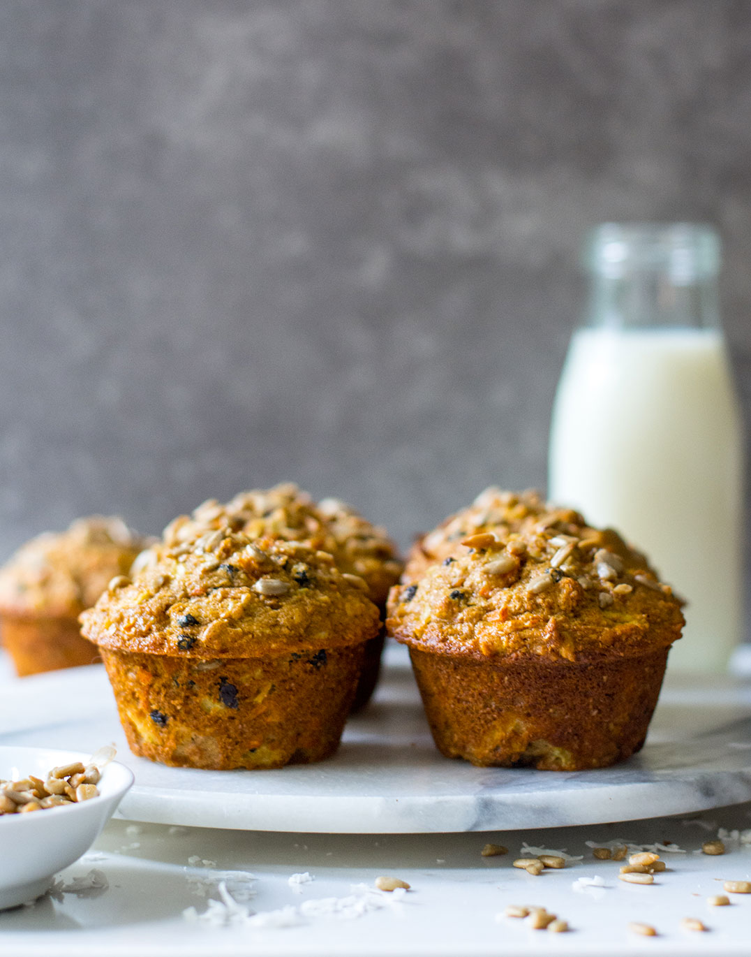 side view of morning glory muffins with milk in background