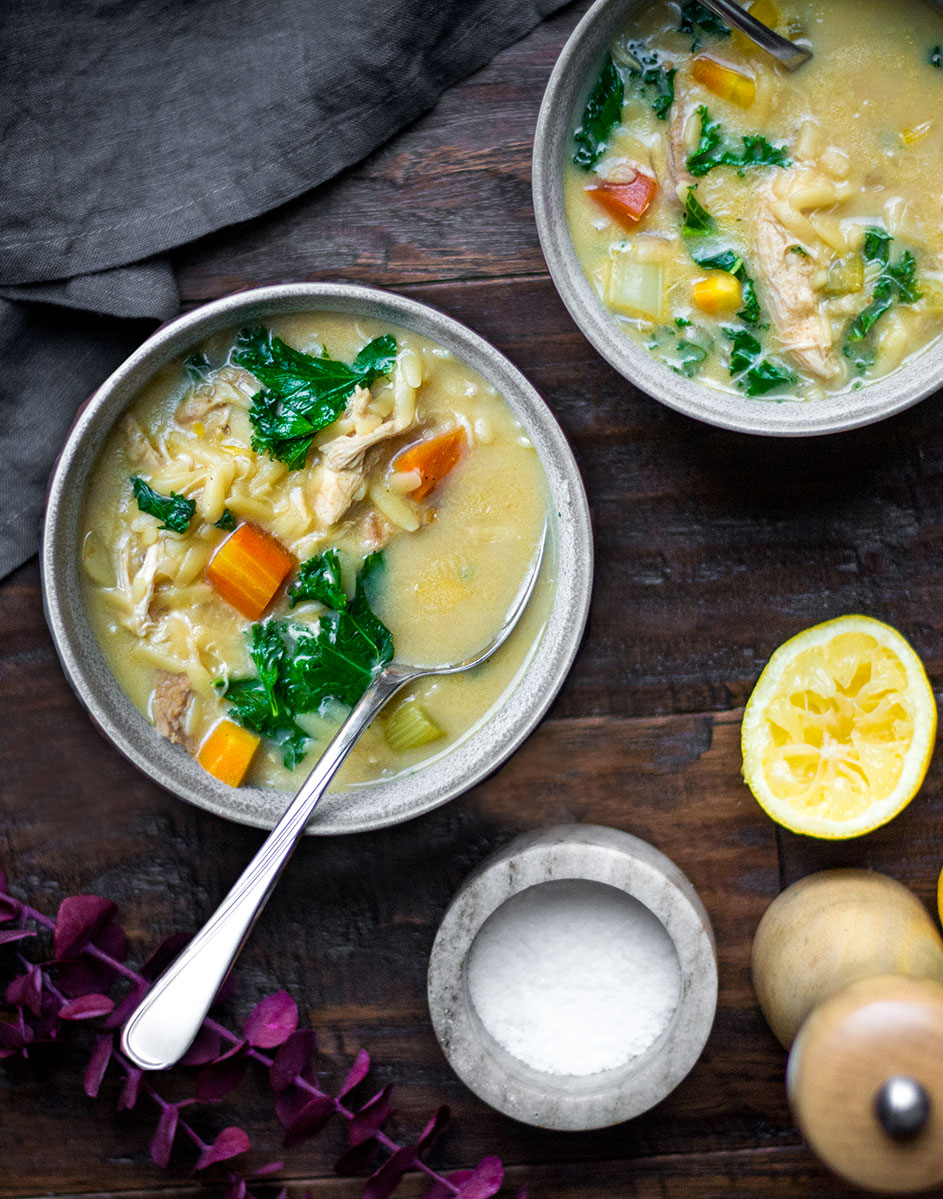 chicken soup in bowls on wooden board with lemons