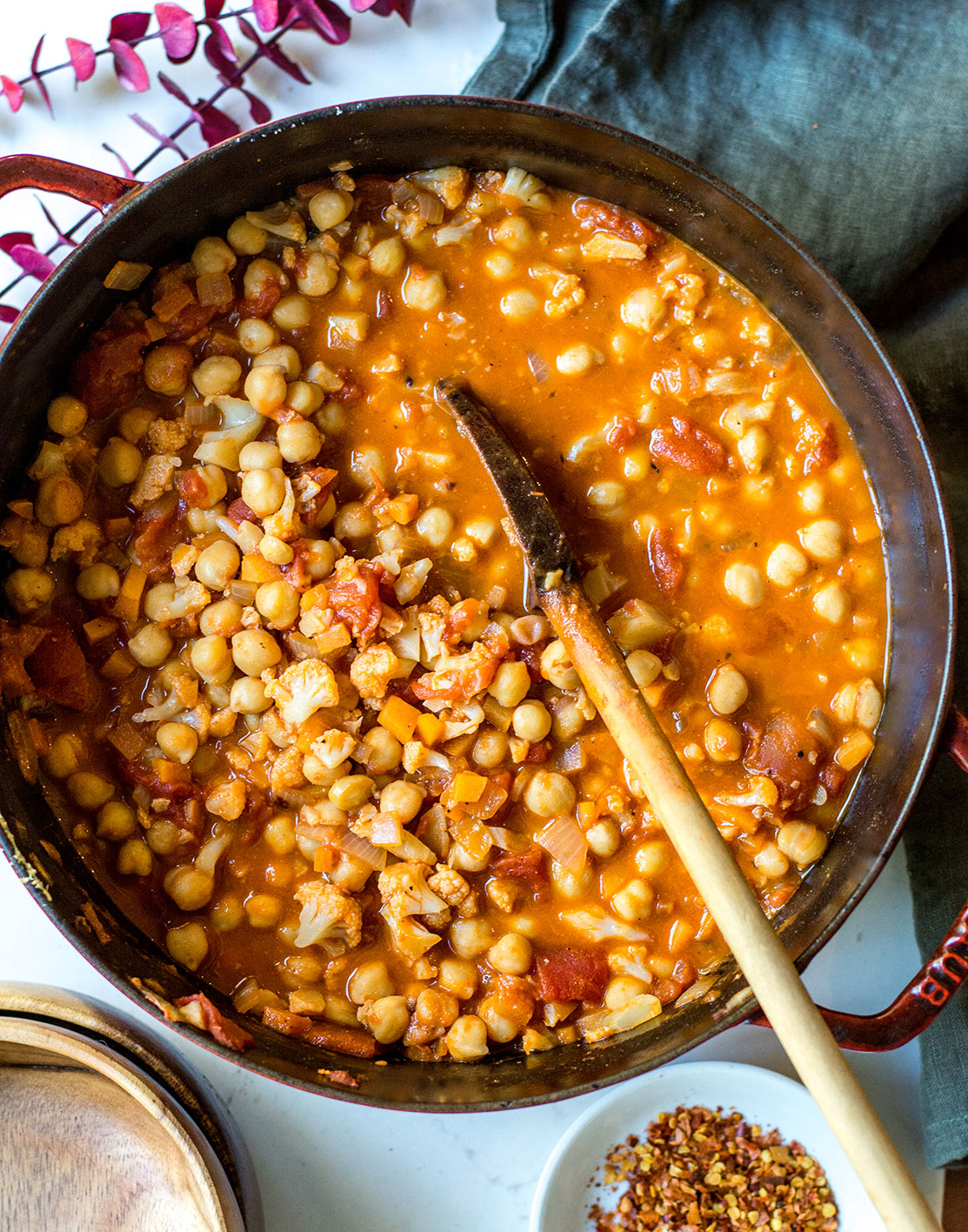Chana Masala Stew in large pot with wooden spoon