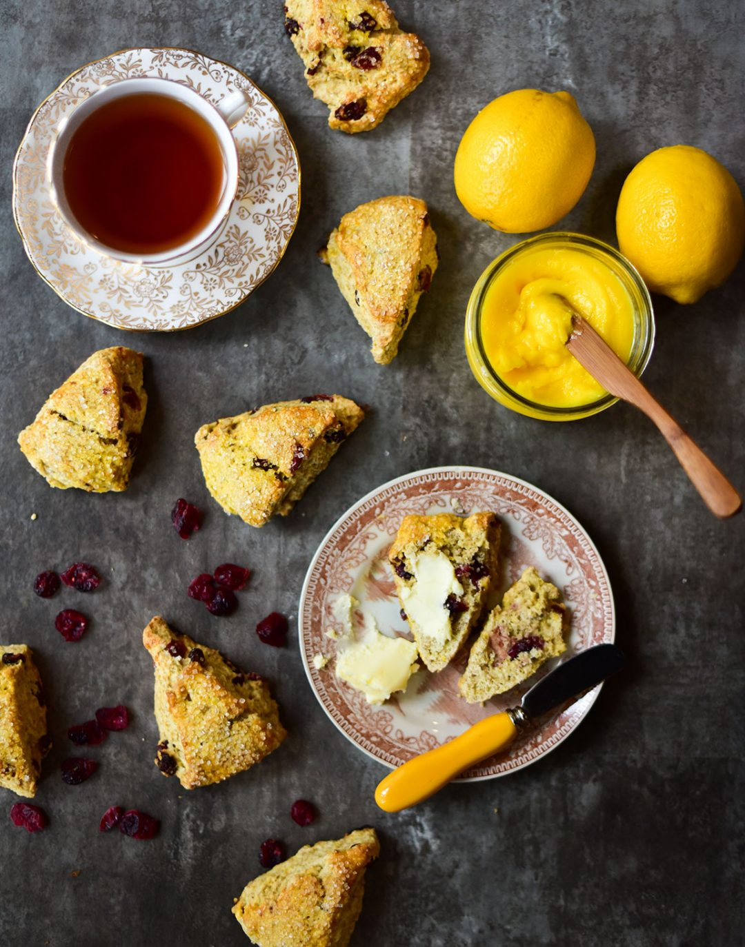 top view of a sliced scone on a brown patterned plate with a bowl of lemon curd and scones on a dark background