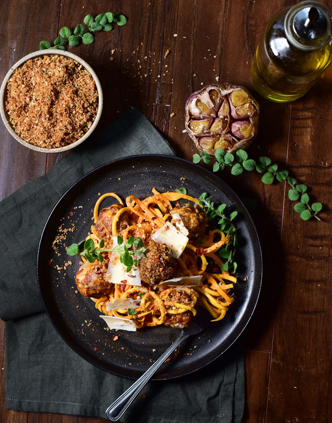 photo of squash pasta on a black plate with meatballs topped with parmesan shavings