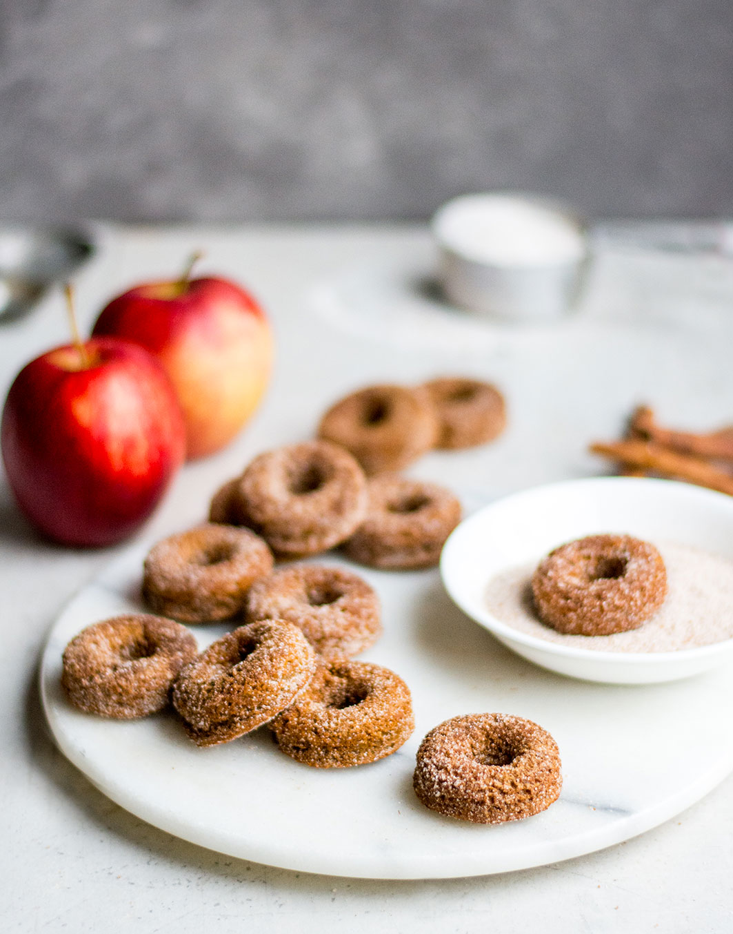 Donuts close up on marble with cinnamon sugar with apples
