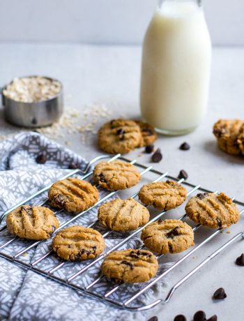 cookies on wire baking rack with milk and oats in background