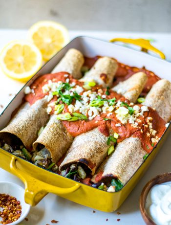 side view of enchiladas with lemons in background
