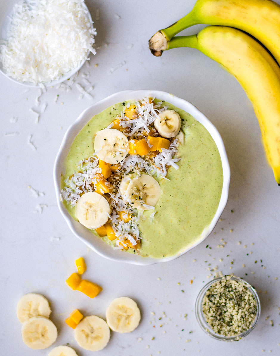 green smoothie bowl on marble counter with bananas and hemp hearts