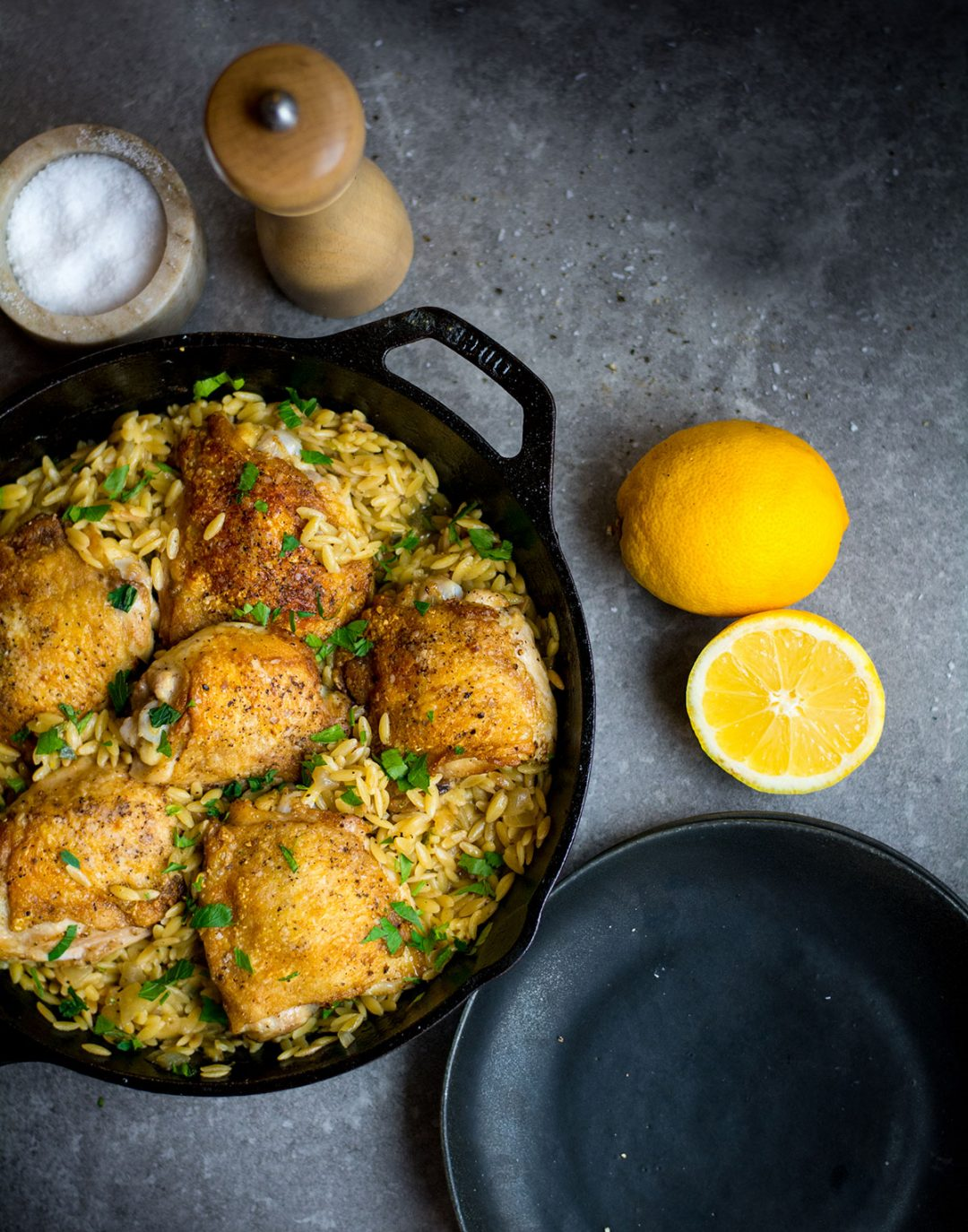 chicken thighs on orzo with lemon in cast iron pan