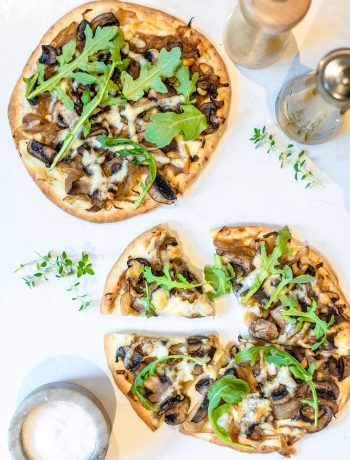mushroom and naan pizzas with arugula on top