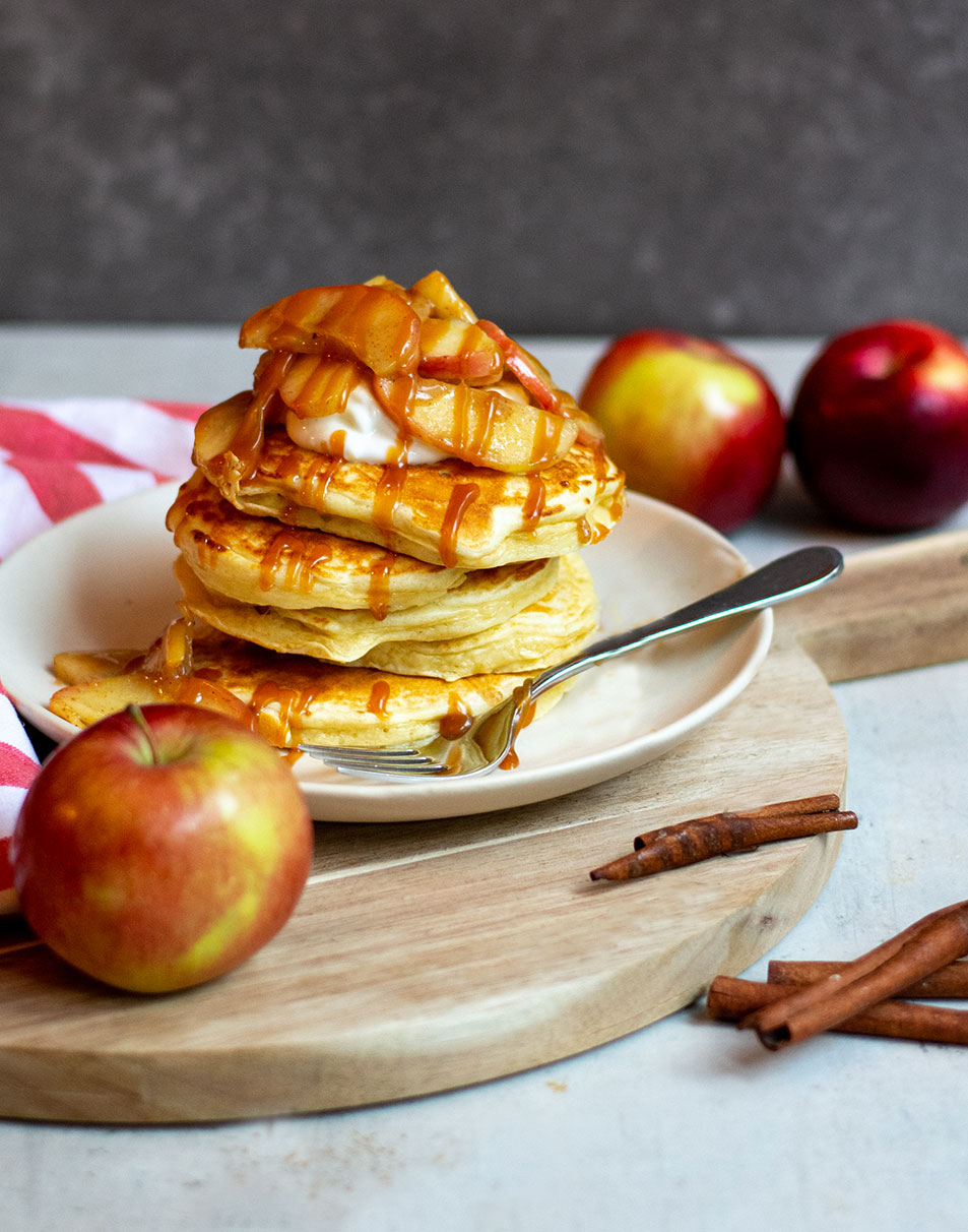 Caramel apple pancakes stacked on plate with caramel drizzle