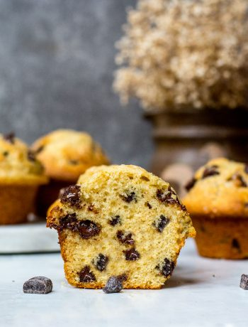 chocolate chip muffin cut in half on table with chocolate chips